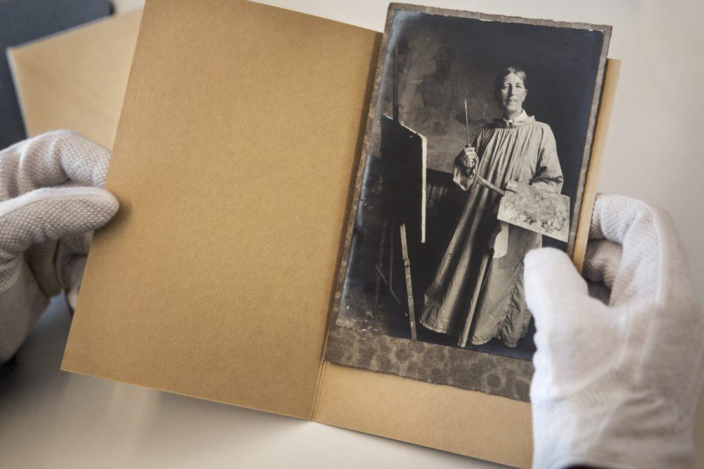 Et par hænder med hvide handsker holder et foto af kunstneren Anna Ancher