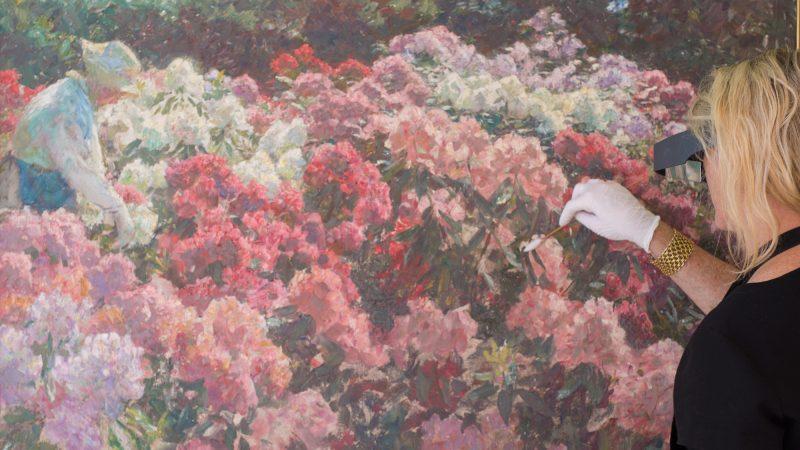 Skagens Kunstmuseers konservator foran Laurits Tuxens maleri 'Rhododendron i Dagminnes have'